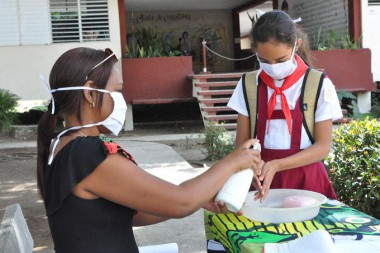 Educadora junto a una pionera mantienen medidas higiénicas.